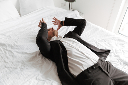 Desperate man dressed in suit lying on bed with arms at his face