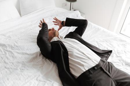 Hombre desesperado vestido con traje acostado en la cama con los brazos en la cara