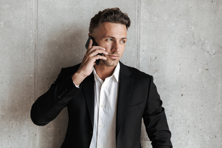 Handsome man dressed in suit talking on mobile phone and looking away over gray wall background