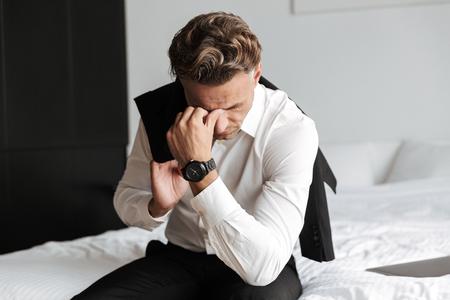 Hombre estresado vestido con traje sentado en la cama y mirando hacia abajo