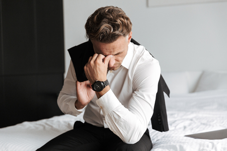 Stressed man dressed in suit sitting on bed and looking down