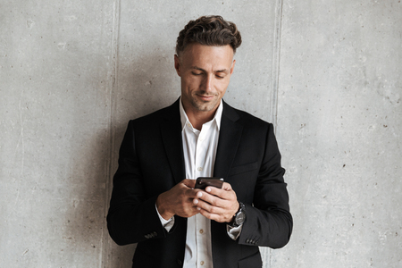 Handsome man dressed in suit holding mobile phone over gray wall background