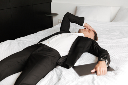 Tired man dressed in suit lying on bed with arms at his face holding laptop