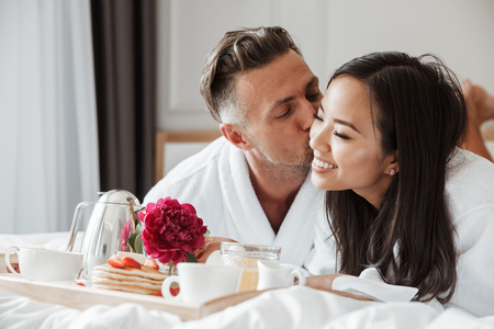 Lovely young couple dressed in bathrobes having romantic breakfast while lying on bed