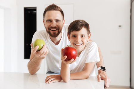 Photo of happy young man father dad holding apples with his son indoors at home.