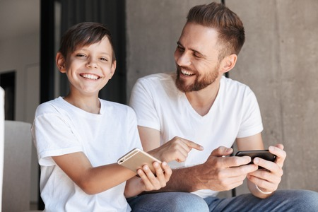 Image of handsome bearded man indoors at home with his son child play games by mobile phone. Boy pointing to fathers phone looking camera.
