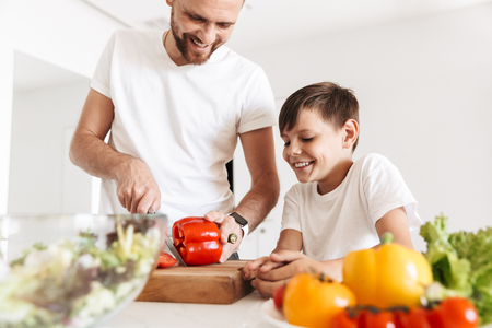 Photo of cheerful young man father dad cooking with his son indoors at home in kitchen.