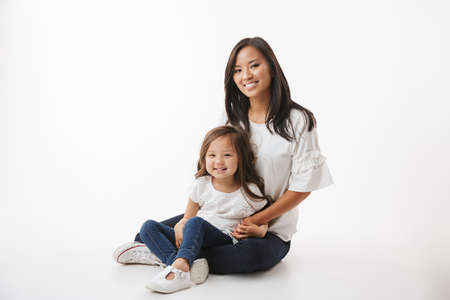 Image of cute young asian woman mother with her little girl child daughter sitting isolated over white wall background.