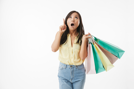 Image of shocked emotional young asian woman isolated over white wall background with shopping bags pointing. Banque d'images - 104510065