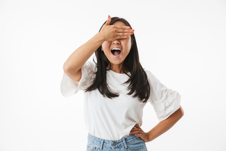 Image of excited young asian woman isolated over white wall background covering eyes with hands. Stock Photo