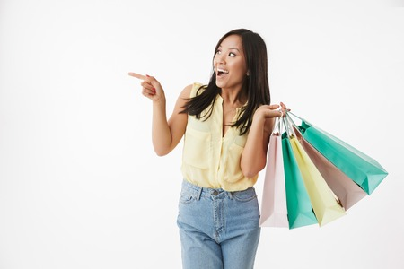 Image of happy emotional young asian woman isolated over white wall background with shopping bags pointing. Banque d'images - 104510214