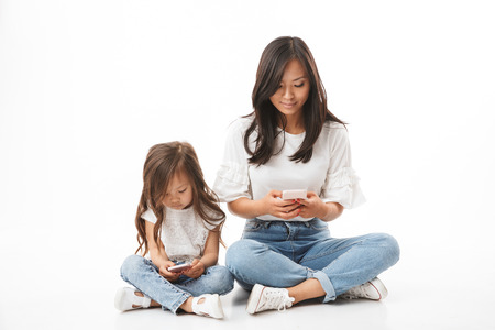 Lovely asian family mother and little daughter holding and using smartphones while sitting on floor together with legs crossed, isolated over white background Stock Photo