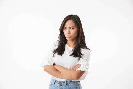 Foto della donna asiatica 20s offesa o arrabbiata che sta con le braccia attraversate e che guarda l'obbiettivo con lo sguardo rigoroso isolato sopra il primo piano bianco del fondo