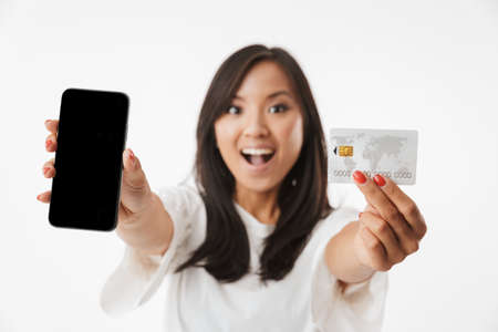 Blurry photo of happy brunette asian woman wearing casual clothing showing at camera credit card and black smartphone isolated over white background
