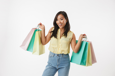 Image of excited young asian woman isolated over white wall background with shopping bags. Stock fotó