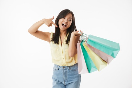 Image of happy emotional young asian woman isolated over white wall background with shopping bags pointing. Banque d'images - 104511027