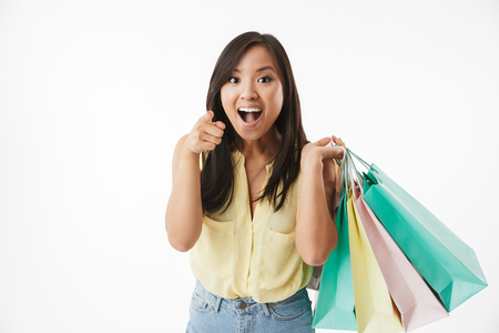 Image of happy emotional young asian woman isolated over white wall background with shopping bags pointing to you. Banque d'images - 104511105