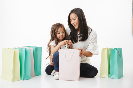 Picture of cute young asian woman mother with her little girl child daughter isolated over white wall background with shopping bags.