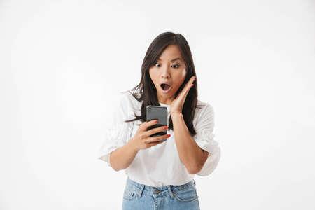 Bild der schockierten oder überraschten asiatischen Frau, die in Panik schreit und gestikuliert, während das Smartphone lokalisiert über weißem Hintergrund betrachtet