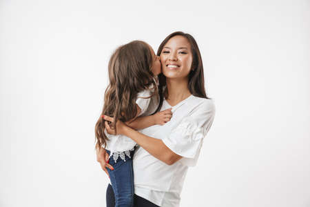 Image of happy young asian woman mother with her little girl child daughter isolated over white wall background.