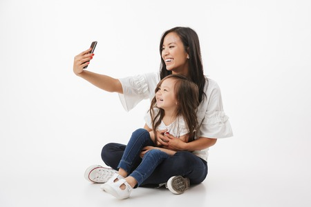 Image of emotional happy young asian woman mother with her little girl child daughter sitting isolated over white wall background make selfie by mobile phone.