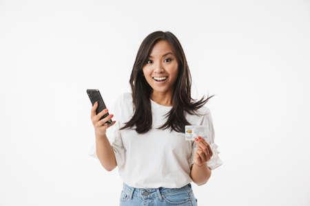 Gioiosa donna asiatica che indossa abbigliamento casual che guarda l'obbiettivo con sorpresa, mentre si tiene la carta di credito e lo smartphone nelle mani isolate su sfondo bianco