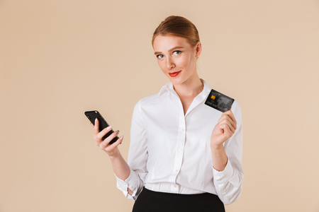 Photo of young business woman standing isolated over beige wall backgound looking camera using mobile phone holding credit card. Stockfoto