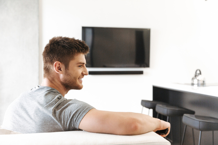 Back view of smiling young man sitting with TV remote control on a couch at home 스톡 콘텐츠