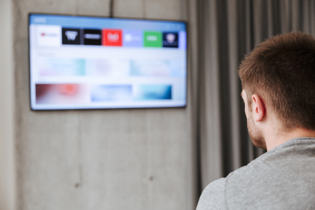 Back view of a man watching smart tv at home