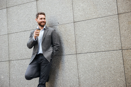Photo of adult attractive man in gray suit and white shirt standing against granite wall and looking aside at copyspace while drinking takeaway coffee 스톡 콘텐츠