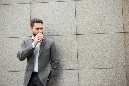 Photo closeup of adult handsome man in gray suit and white shirt standing against granite wall and looking aside at copyspace while drinking takeaway coffee