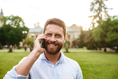 Happy photo of smiling adult man 40s in white shirt looking at you while talking on black smartphone during walk in green park
