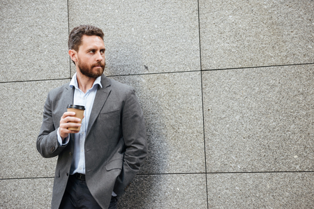 Photo closeup of adult concentrated man in gray suit and white shirt standing against granite wall and looking aside at copyspace with takeaway coffee in hand