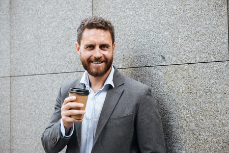 Portrait closeup of bearded handsome man 40s in gray suit and white shirt standing against granite wall and smiling at camera while drinking takeaway coffee 스톡 콘텐츠