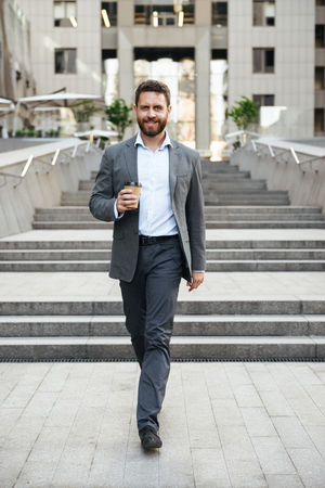 Photo of pleased entrepreneur man 40s in gray suit walking down stairs of modern business center with takeaway coffee in hand