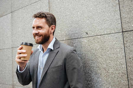 Portrait closeup of adult handsome man in gray suit and white shirt standing against granite wall and smiling while drinking takeaway coffee