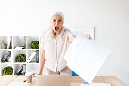 Furious mature business woman showing blank paper documents while standing at the desk