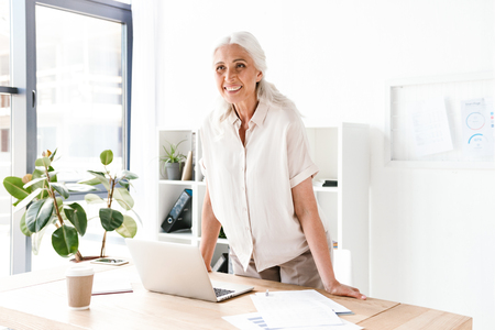 Happy mature business woman leaning on desk with laptop computer while standing and looking away in office