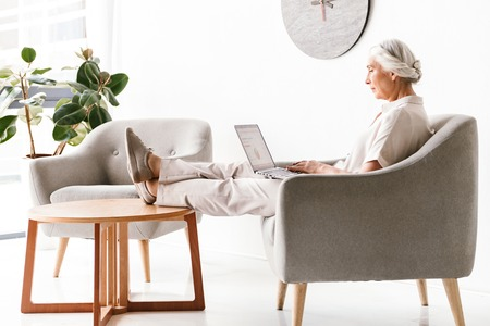 Side view of confident mature business woman working on laptop computer while sitting in armchair indoors Stock Photo