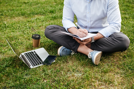 Cropped photo of caucasian man in business clothing sitting on grass in park with legs crossed and writing down notes in notebook while working on laptop