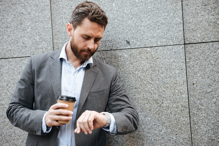 Photo closeup of adult businessman in gray suit and white shirt standing against granite wall and looking at wrist watch while drinking takeaway coffee
