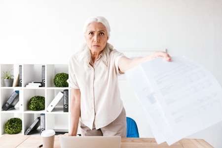 Angry mature business woman showing blank paper documents while standing at the desk