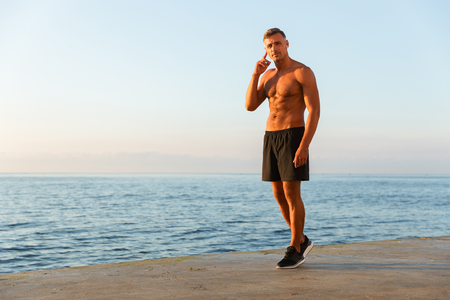 Full length of handsome shirtless sportsman with earphones at the beach Foto de archivo - 106508020