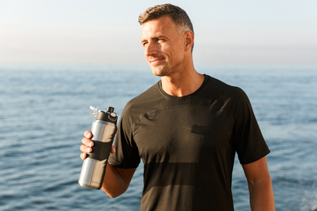Photo of handsome strong mature sportsman standing with bottle of water drinking on the beach.