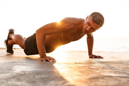 Confident sportsman doing push-ups at the beach in sunlight 스톡 콘텐츠