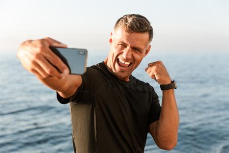 Vrolijke knappe shirtless sportman die een selfie neemt terwijl hij op het strand staat en zijn biceps buigt