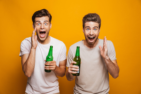 Portrait of a two happy young men best friends holding beer bottles and shouting at camera isolated over yellow background Banque d'images
