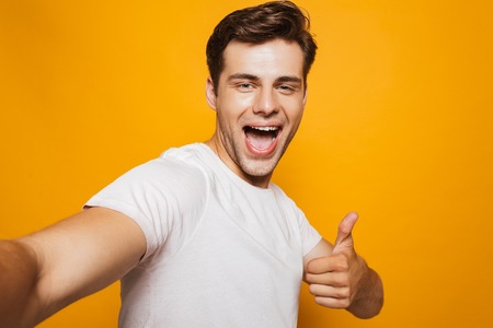 Portrait of a happy young man taking a selfie with outsretched hand, showing thumbs up gesture isolated over yellow background