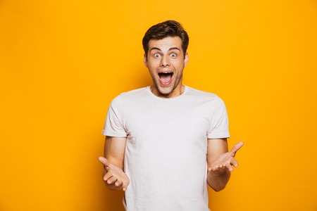 Portrait of an astonished young man celebrating success isolated over yellow background