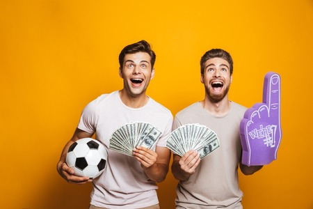 Portrait of a two cheerful young men best friends with soccer ball showing money banknotes and shouting isolated over yellow background Фото со стока